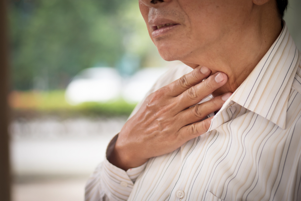 Elderly person touching their throat after feeling pain